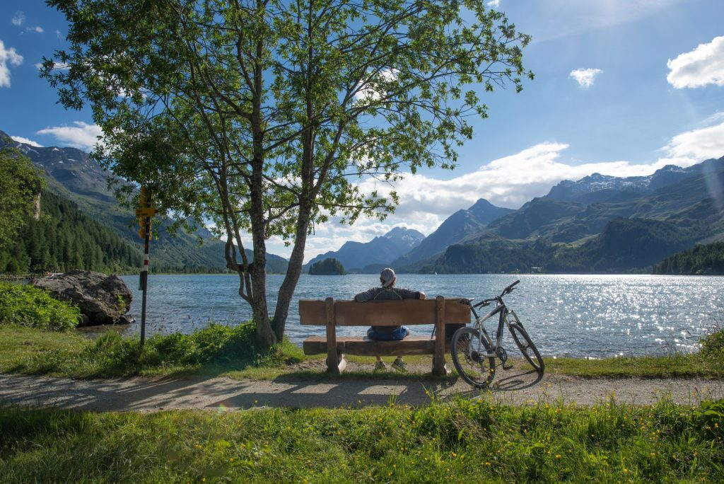 A biker rests looking at the view on a bench