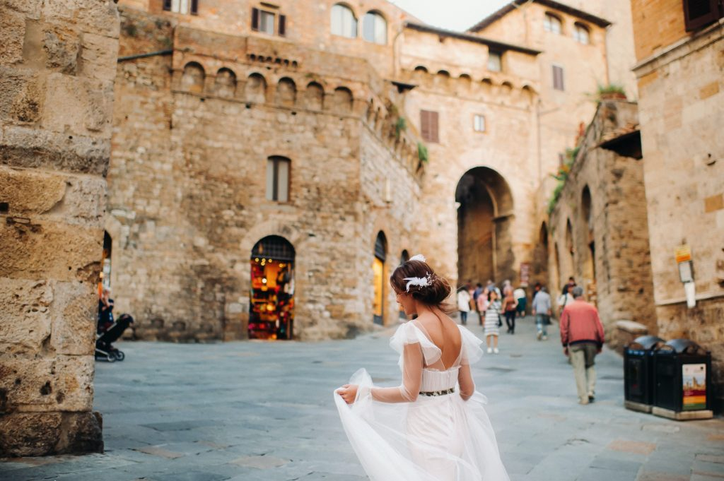 A bride in a white dress in the old town of San Gimignano.A girl walks around the city in Italy