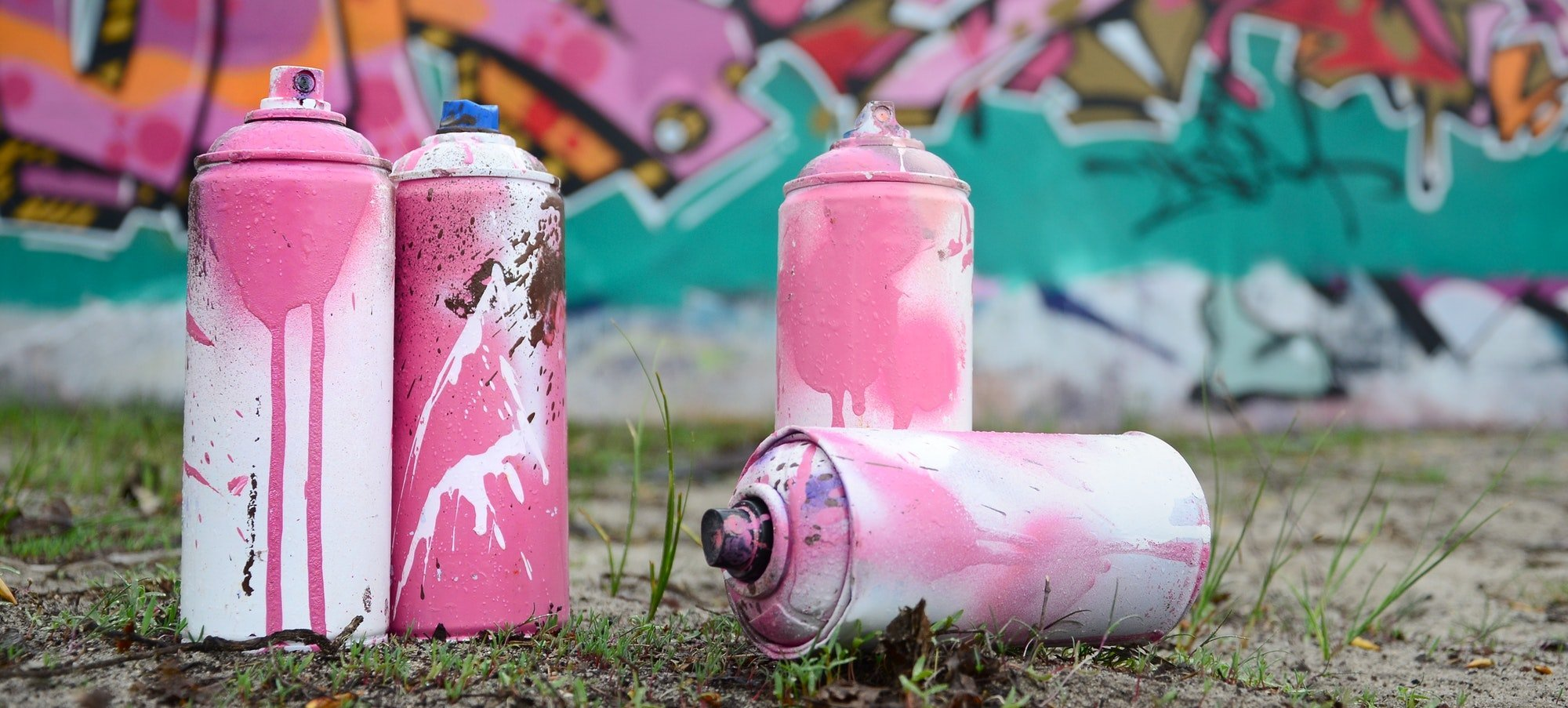 A few used paint cans lie on the ground near the wall with a beautiful graffiti painting in pink and