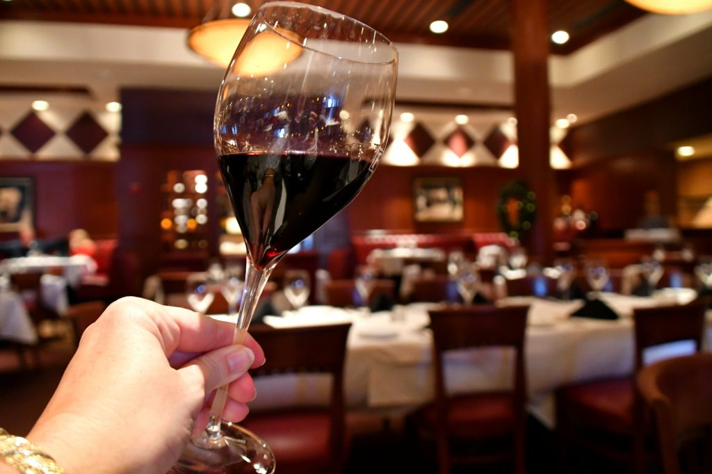 A woman holding up a glass of red wine in a restaurant to examine its color quality
