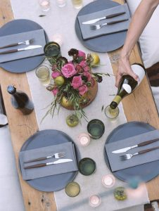 Apple orchard. A set table, a person pouring a glass of wine.