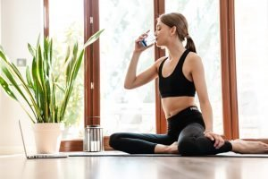 Attractive tired young fitness woman drinking water