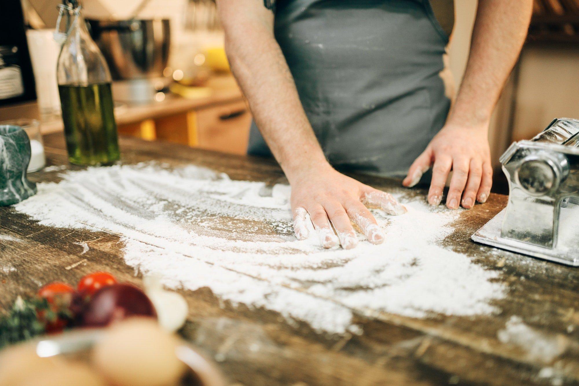 Chef in apron, flour,eggs, pasta machine on table