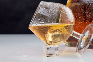 Close-up glass of brandy with ice cubes.