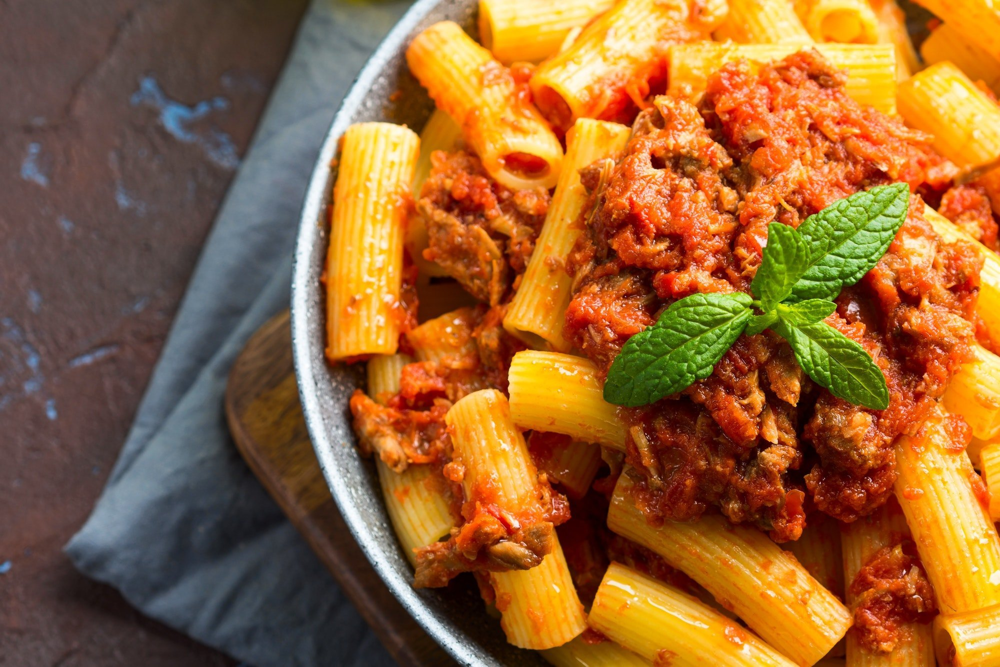 Delicious rigatoni pasta with italian tomato meat ragu sauce served in a pan on dark brown