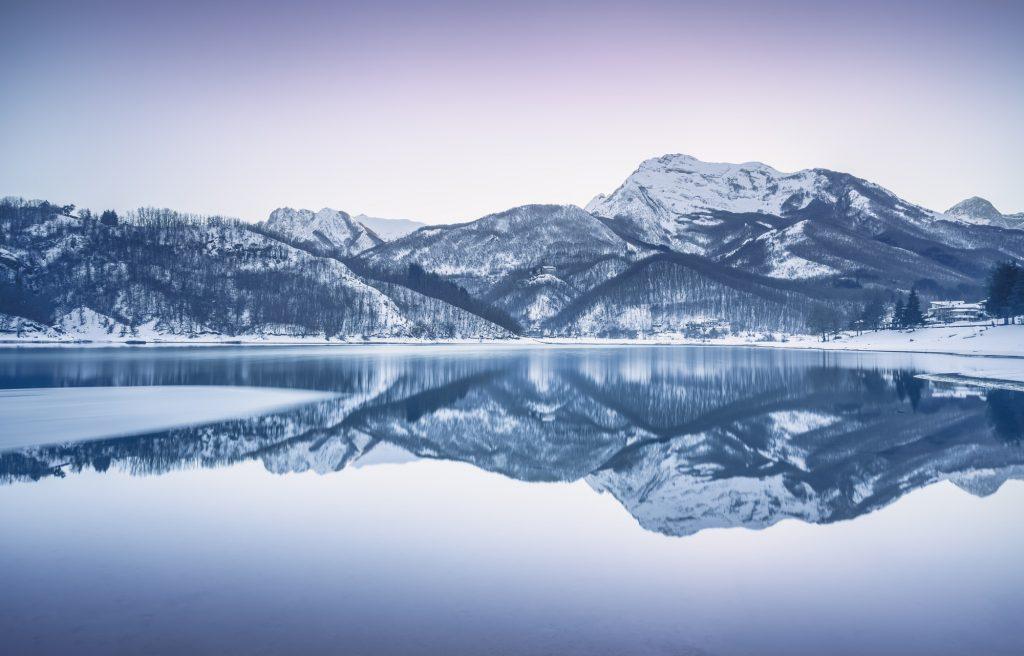 Gramolazzo iced lake and snow in Apuan mountains. Garfagnana, Tuscany, Italy