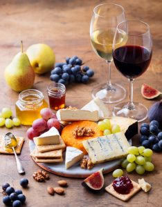 Grape, Cheese, Figs and Honey with a Glasses of Red and White Wine on a Wooden Background.