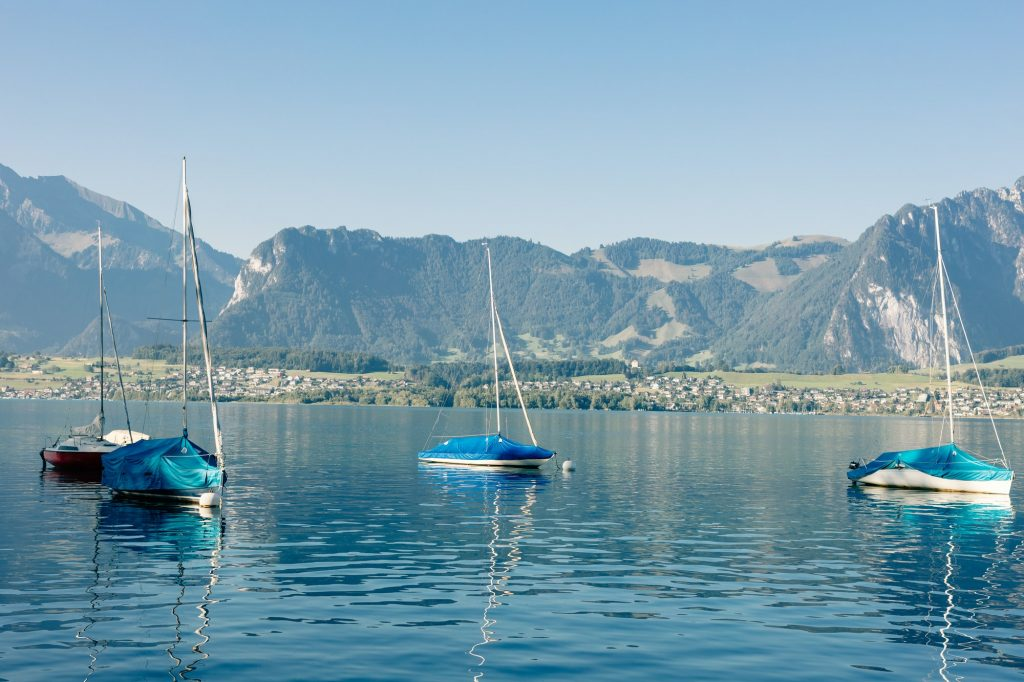 lake with yachts and mountains landscape