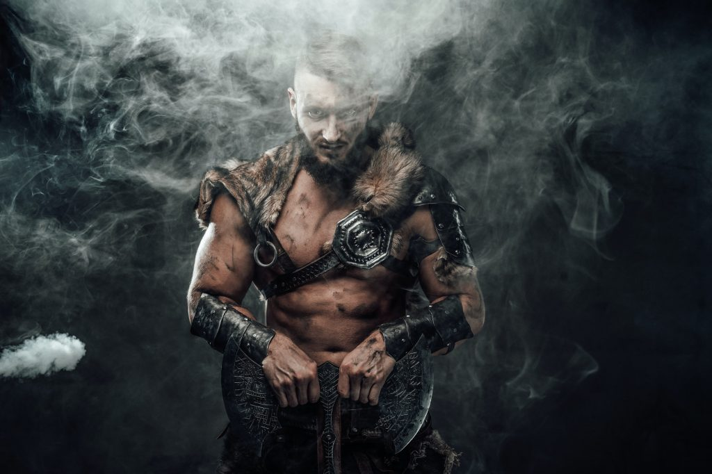 Nordic barbarian in light armour in smokey background with axe