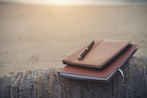 Notebooks,books and pen on the beach.