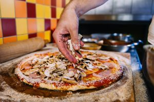 Putting Mushrooms On Pizza In Pizza Restaurant