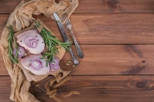 Raw chicken thighs with rosemary, red onion and peppercorns