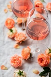Rose wine in glasses and roses on white background, flat lay
