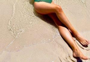 Suntanned legs on a Sandy Beach