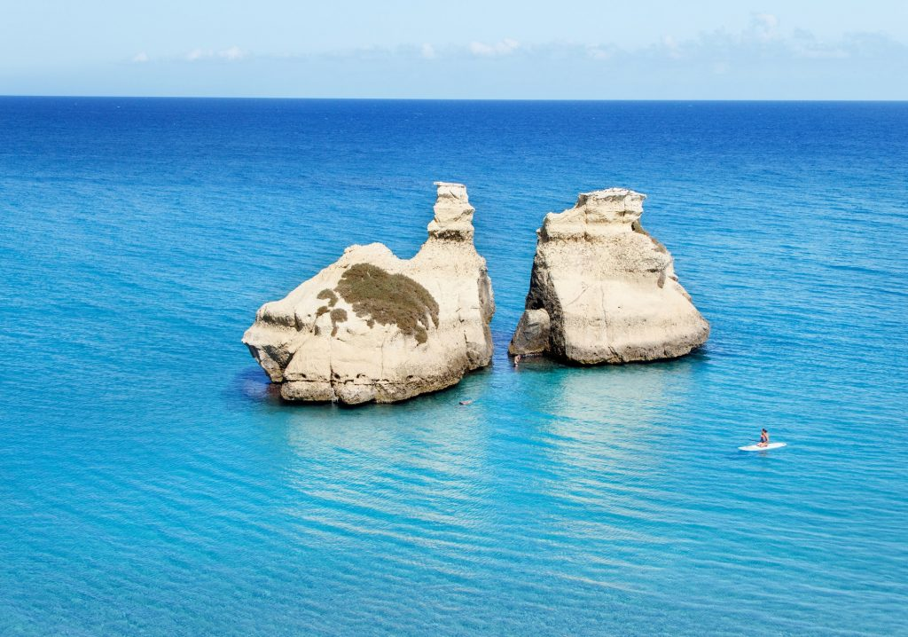 The Two Sisters stacks in front of the shore of Torre dell'Orso