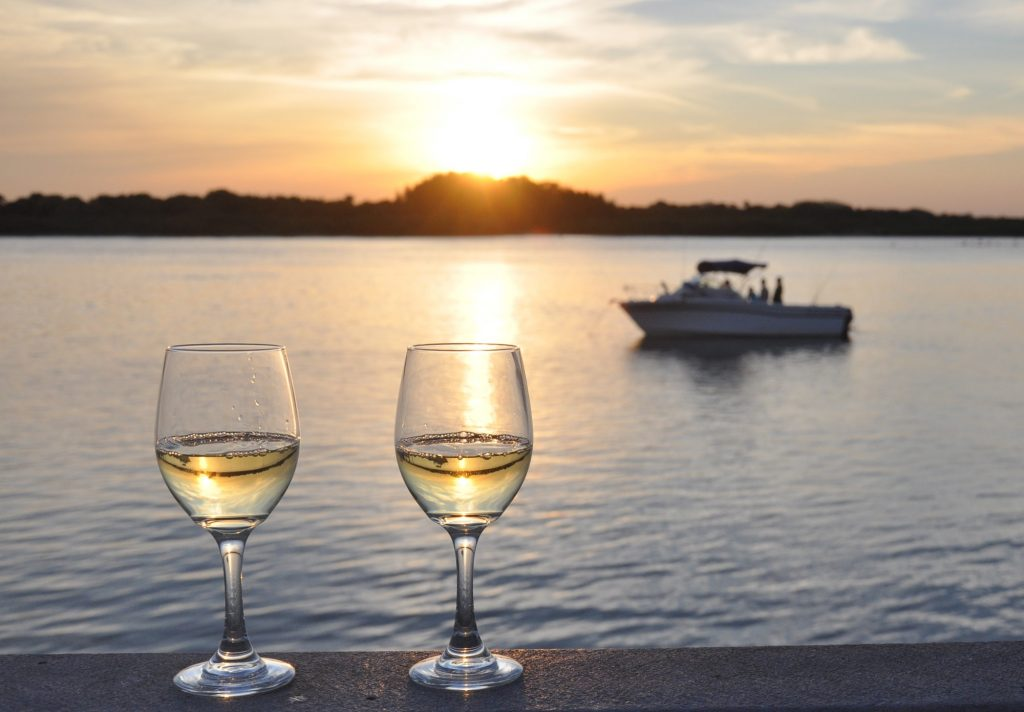 Two glasses of white wine in front of a boat on the ocean at sunset