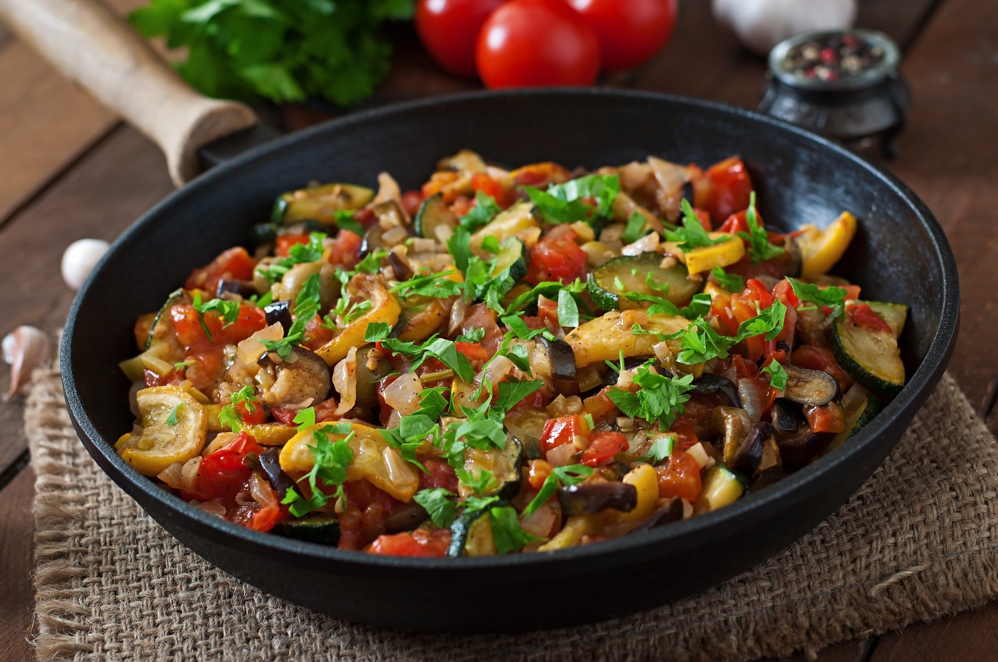Vegetable Ratatouille in frying pan on a wooden table.