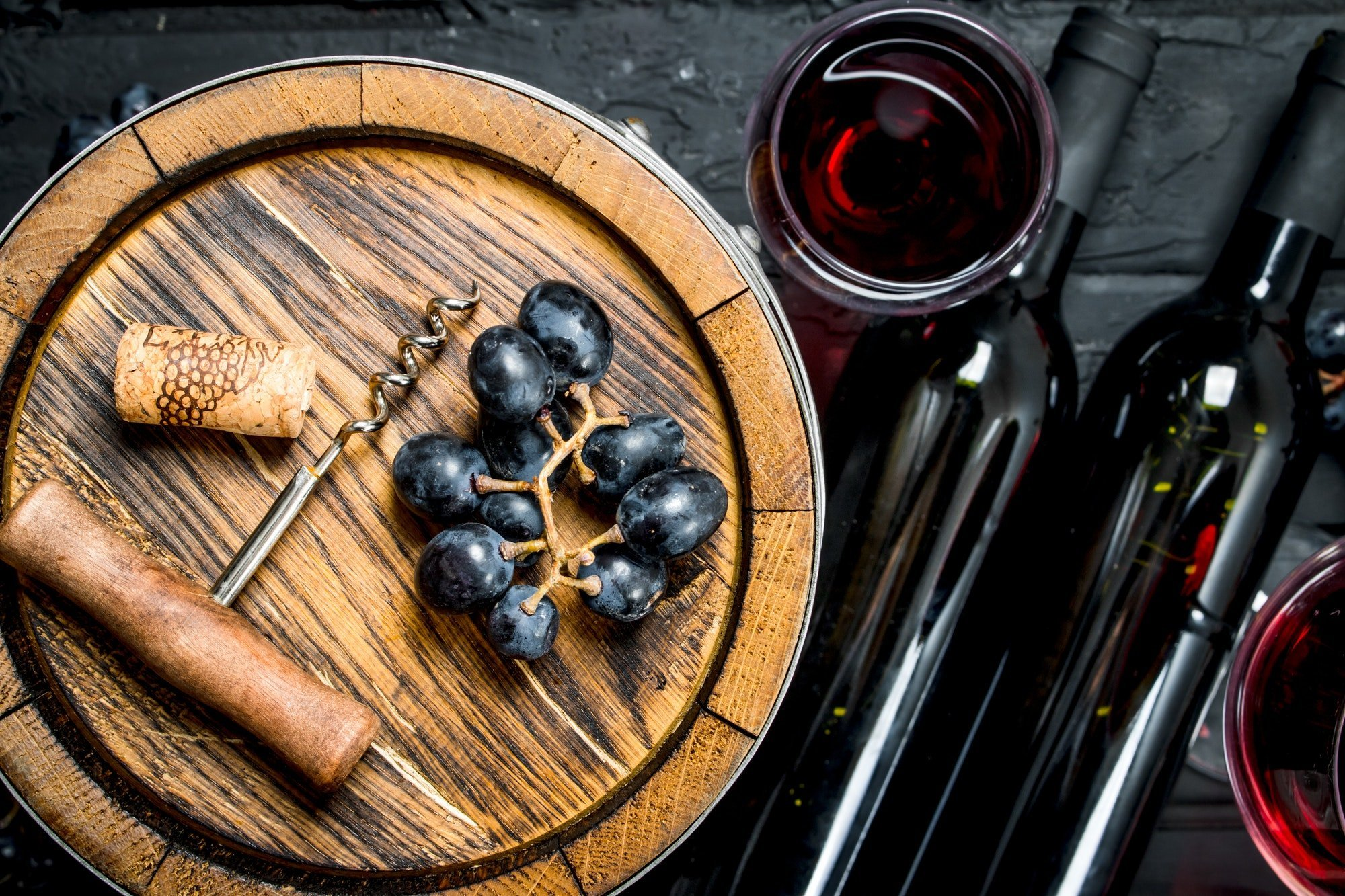 Wine background. Red wine with grapes and an old barrel.