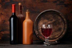 Wine bottles and old wooden barrel