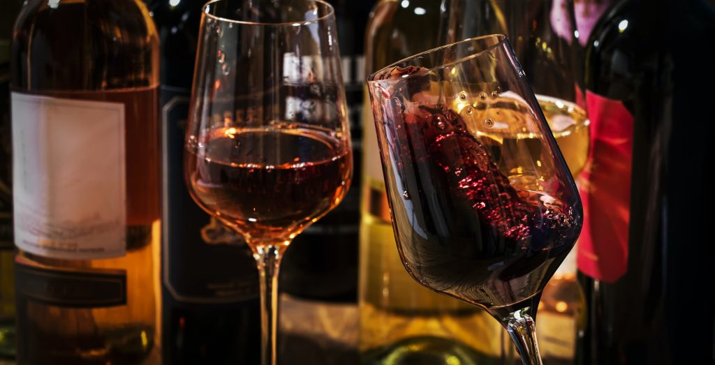 Wine tasting. Red wine shaking in glass on background with selection of red, white and rose wines
