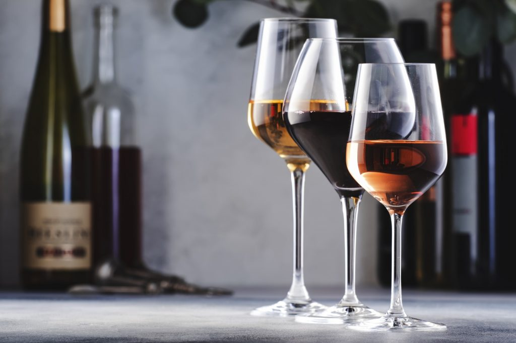 Wines assortment. Red, white, rose wine in wineglasses and bottles on gray background.
