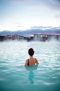 Woman relaxes and enjoys of spa in hot spring Blue Lagoon in Ice