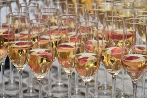 Group of glasses with champagne and strawberries at the buffet table at a party