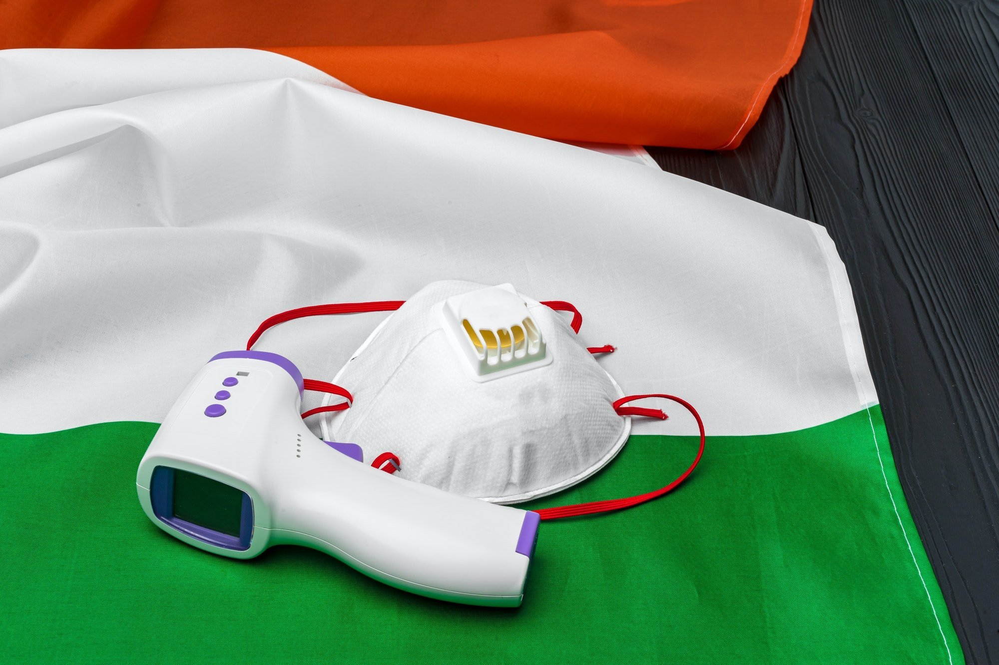 Medical face mask and contactless thermometer on flag of Italy