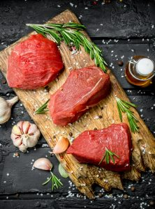 Raw meat. Sliced pieces of beef with spices and herbs on a wooden Board.
