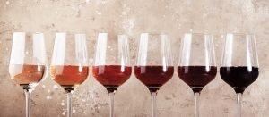 Rose wine glasses on the beige table. Rosado, rosato or blush wine tasting concept