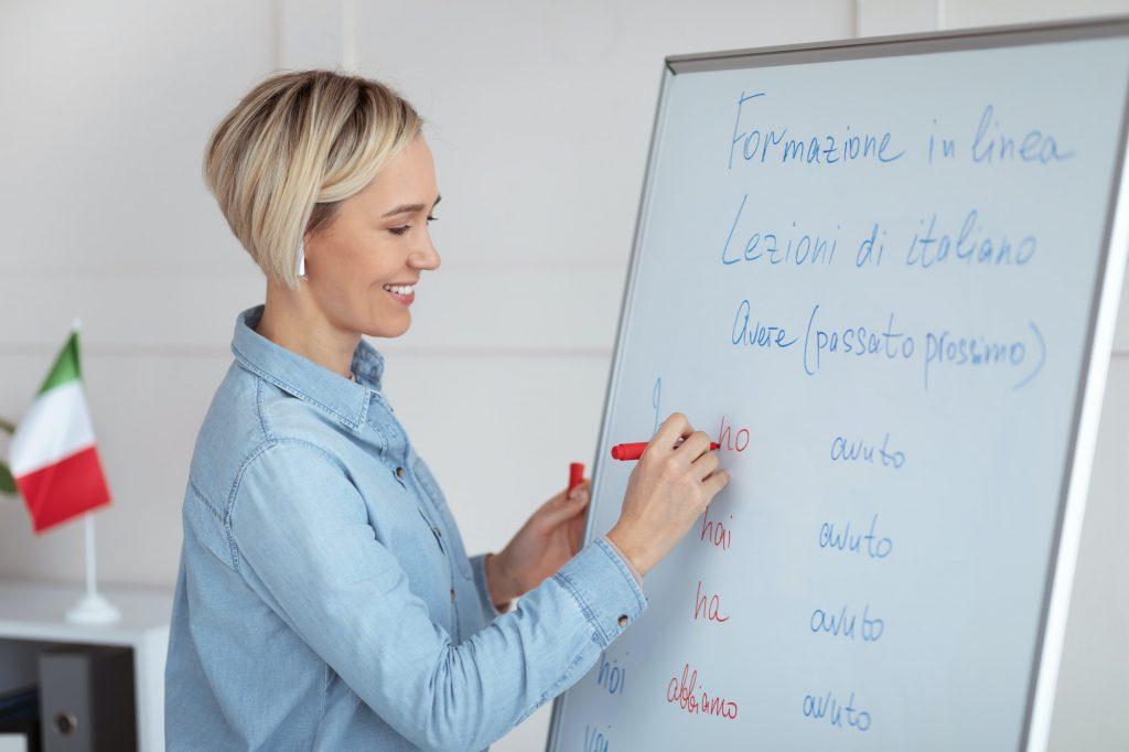 Teaching foreign languages online. Cheerful female teacher giving Italian class, writing down basic