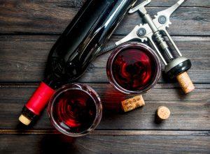 Wine background. Red wine with corkscrew.