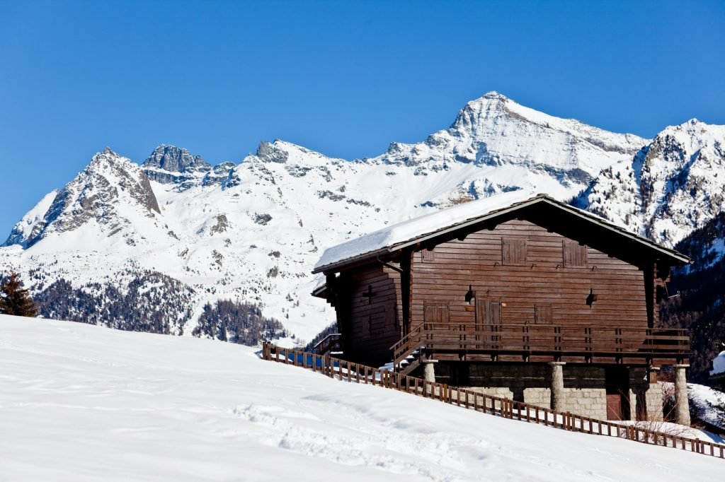 Wooden cottage over snowed mountain