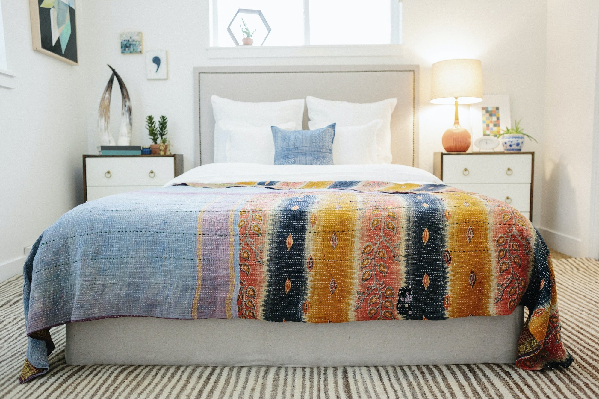 A bedroom with a vivid striped patterned bedspread.
